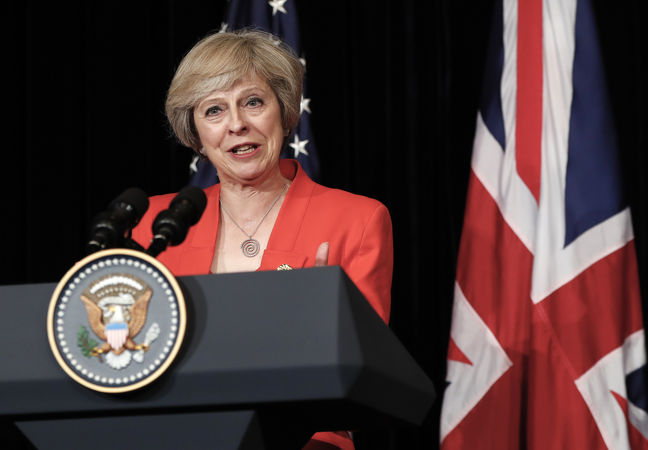UK PM May charts collision course with Brexiteers over immigration