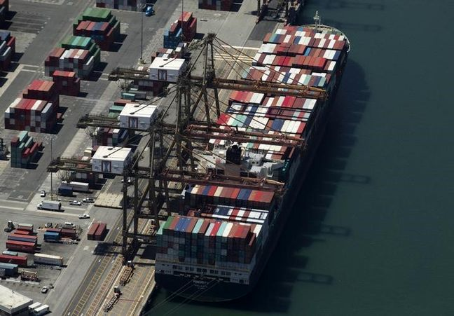 U.S. economy slows on wider trade gap; business spending rises